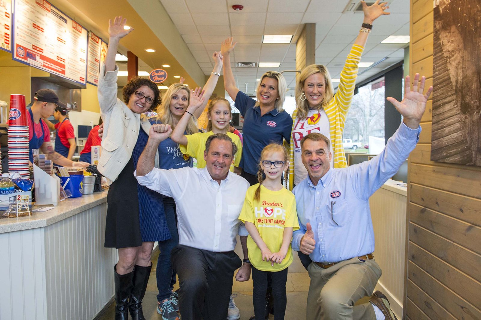 Jersey Mike's Founder & CEO Peter Cancro (kneeling, left) celebrated the company's 8th Annual Day of Giving with Callyn Stanley (front center) and Area Director Mike Spiegel at the Olathe, Kansas, restaurant. They were joined by (back row, from left) Shelia Montgomery, Deliece Hofen, founder of local charity partner Braden's Hope, Taylor Stanley, Tatiana Voevodina Cancro, and Kim Stanley.