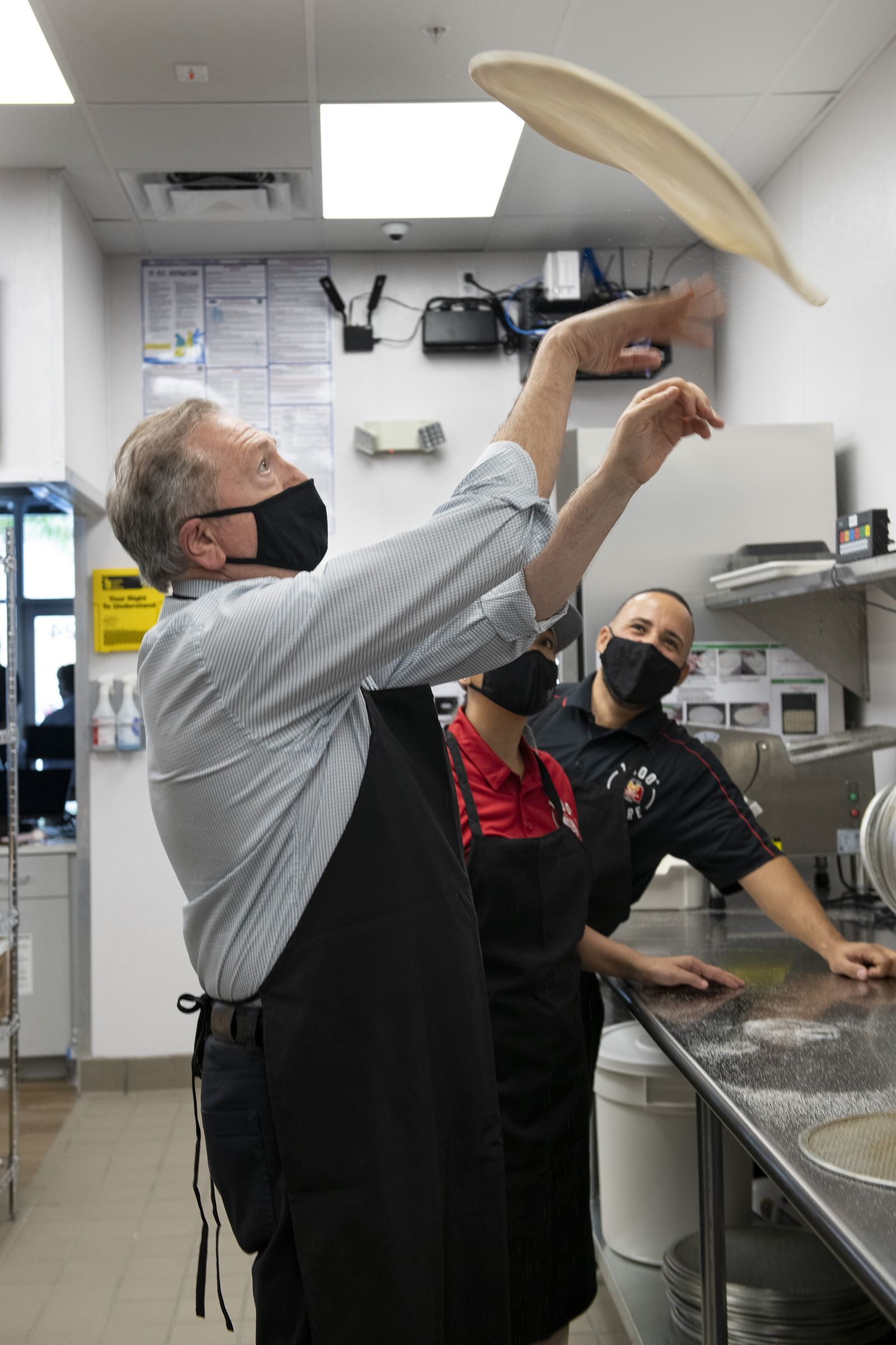 Marco's Pizza founder Pasquale Giammarco, foreground, demonstrates his pizza-tossing skills to franchisees Kattya Barbaran and Rafi Vargas Tuesday, October 20, 2020 in Kissimmee, Fla. The store is the 1000th franchise store opened by the pizza brand. Both Varga and Barbaran are residents of Kissimmee.
