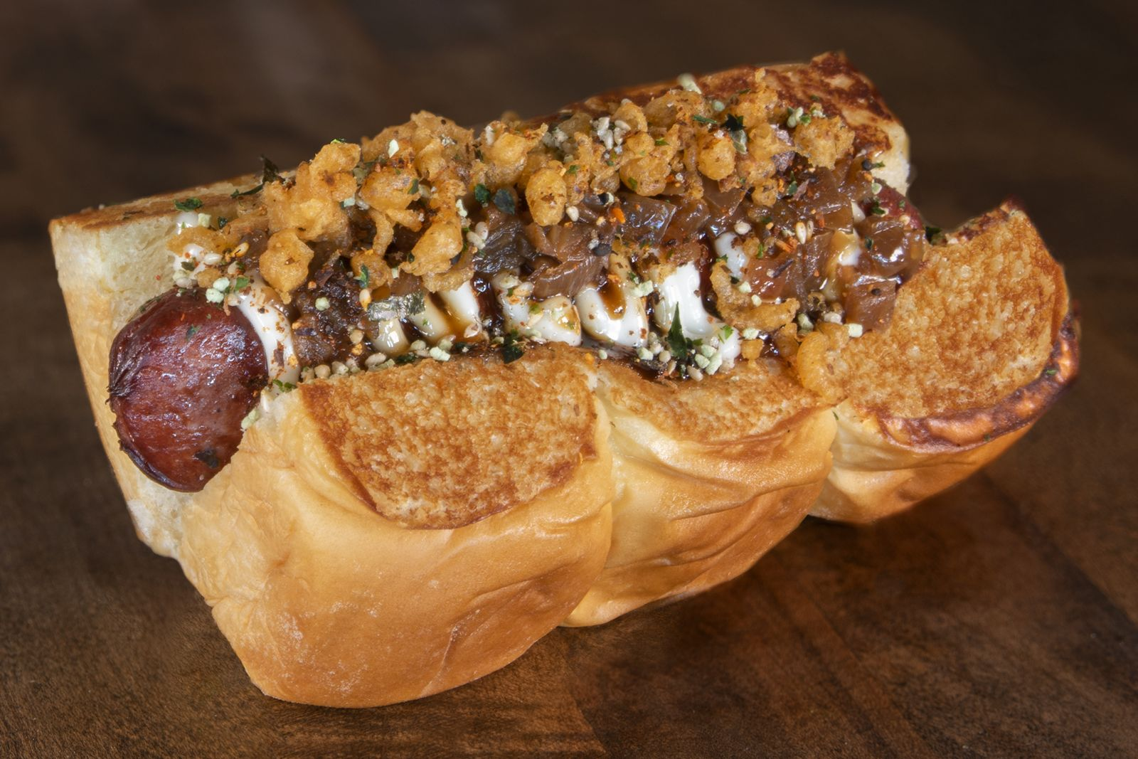 Mr. Miyagi - a deep-fried beef dog topped with mayo, teriyaki sauce, caramelized onions, tempura crumbles and wasabi furikake, served on grilled King's Hawaiian rolls.